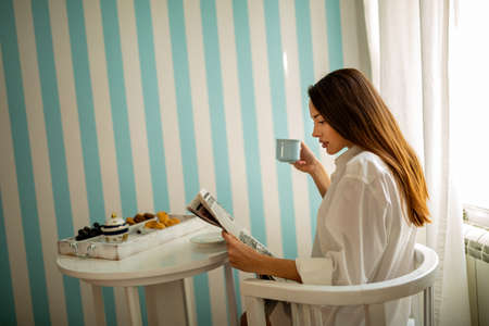 Portrait of a young woman reading the news while having coffee in her kitchen 版權商用圖片