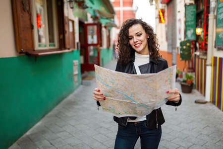 Cheerful woman searching direction on location map while traveling 版權商用圖片