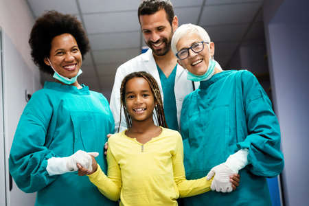 Team of experienced highly qualified doctors with child patient after a successful treatment