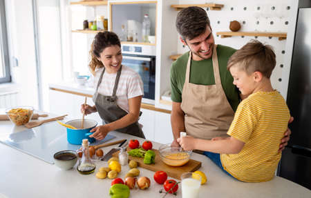 Happy family in the kitchen having fun and cooking together. Stockfoto