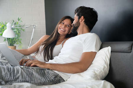 Romantic happy couple in love relaxing at home having fun. People technology concept.