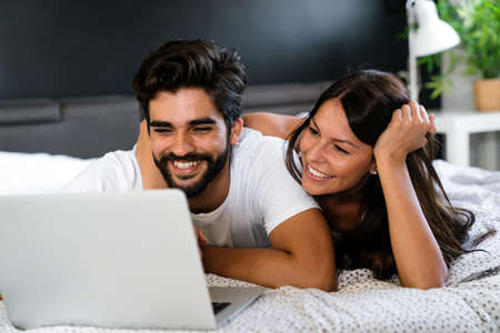 Young couple relaxing at home with laptop. Love, happiness, people and fun concept. 免版税图像