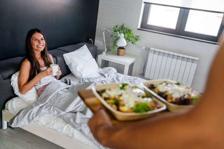 Men brings breakfast to bed for his beautiful girlfriend. Couple, love concept