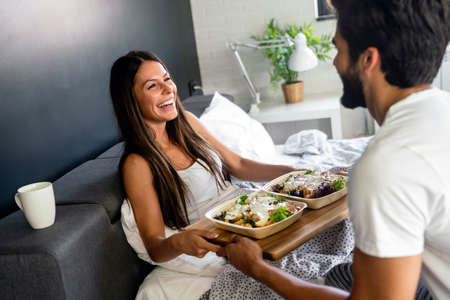 Happy man bringing the breakfast to his girlfriend on the bed 免版税图像