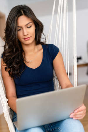 Happy beautiful woman using technology device to work, study at home. Social media time.