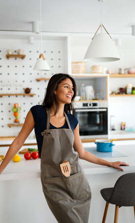 Young beautiful woman cooking healthy food in the kitchen. Healthy lifestyle, food, diet concept 免版税图像