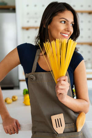 Sporty young woman is preparing healthy food in kitchen
