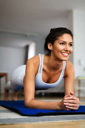Fit sport woman exercising and training at home 免版税图像