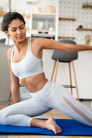 Sporty beautiful woman exercising at home to stay fit