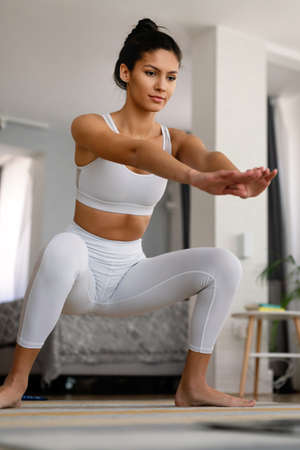 Young fit woman in sportswear watching online video with fitness exercises on laptop