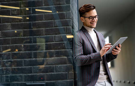 Happy young business man with tablet at work in modern urban background