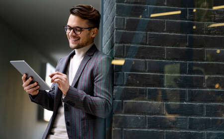 Portrait of successful man using digital tablet in urban background. Business people concept