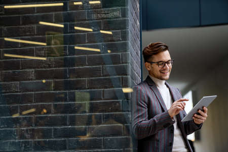 Successful happy business man working on digital tablet in urban background