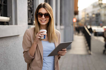 Portrait of a successful woman using digital tablet during quick break in urban background