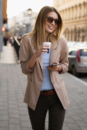 Portrait of happy business woman with coffee and digital tablet on her way to work on city street.