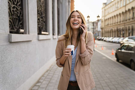 Attractive businesswoman drinking a coffee and using a mobile while enjoying break 免版税图像