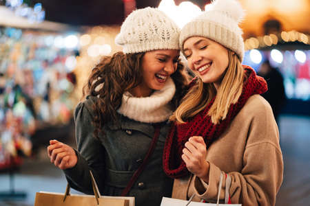 Happy women friends having fun and shopping at Christmas. Sale xmas people happiness concept