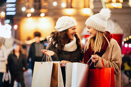 Happy women friends are shopping for presents at Christmas. People holiday sale shopping concept 免版税图像