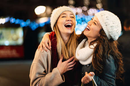 Happy women talking and laughing outdoor in city at Christmas. Happiness shopping people concept