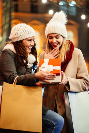 Happy women friends exchanging gifts for Christmas. Shopping happiness sale people concept