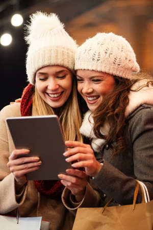 Happy women friends looking at digital tablet PC. People shopping online technology tourism concept 免版税图像