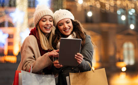 Happy women friends using digital tablet for online shopping at Christmas in the city. 免版税图像