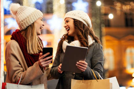 Women friends enjoy the night in shopping at Christmas. Sale, people digital tablet concept 免版税图像
