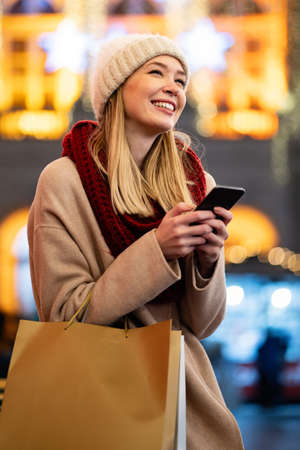Shopper woman buying online on the smart phone at Christmas. People shopping communication concept