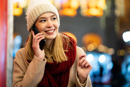 Portrait of young smiling beautiful woman using smartphone on the street at winter