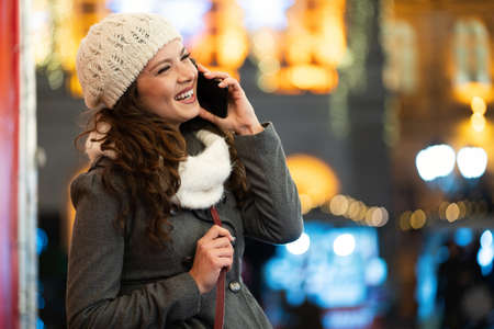 Happy woman using a mobile phone in the street in winter. Christmas communication people concept