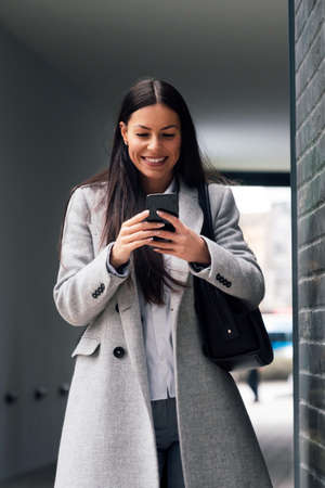 Successful businesswoman or entrepreneur using smartphone while walking outdoor 免版税图像