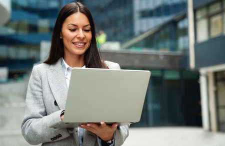 Successful businesswoman or entrepreneur working with notebook outdoor