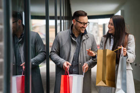 Portrait of happy couple with shopping bags on the street outdoor. Christmas sale people concept
