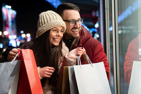 Portrait of happy smiling couple with Christmas presents in the city. Shopping sale people concept 免版税图像