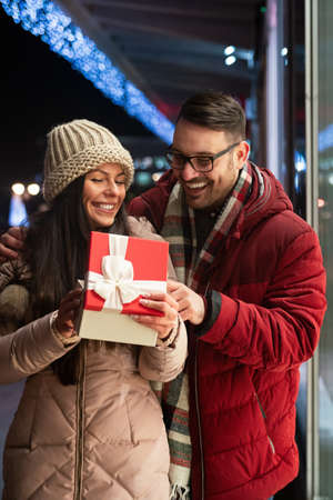 Young couple in love is celebrating with gift. Christmas birthday valentines day present concept