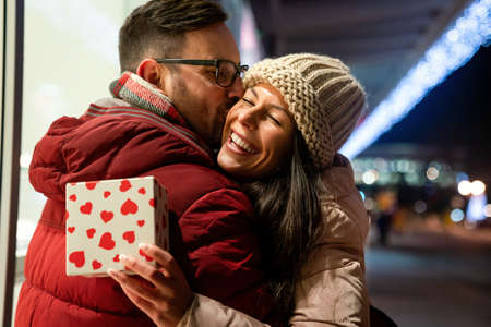 Happy young couple in love celebrating with a gift. People christmas valentine day birthday concept