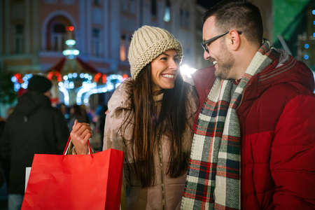 Romantic Christmas shopping. Happy young couple buying gifts for family. Sale and people concept. 免版税图像