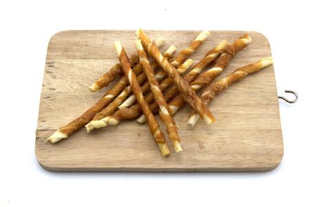 Chicken Munch sticks on Chopping Wood on White Background  Dog Food