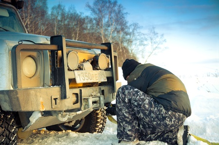 Land Rover Defender 110 suv and man tying tow rope. Car on background the Russian winter. February 19, 2011. Mattrazz Trophy # 18