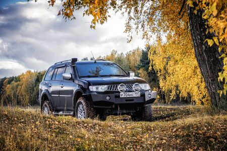 Mitsubishi Pajero Sport and trees in autumn on a sunny day. Moscow, Russia. October 8, 2017 Editorial
