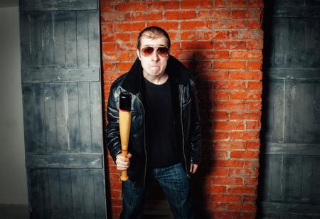 Boze man met vleermuis op bakstenen muur achtergrond. Russische gangster jaren 90 Stockfoto