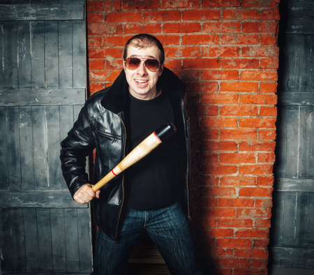Angry man with bat on brick wall background. Russian gangster 90s Stockfoto