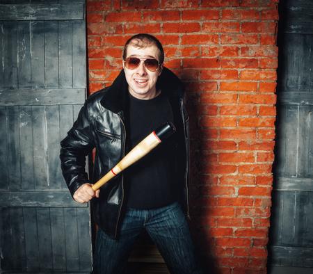 Boze man met vleermuis op bakstenen muur achtergrond. Russische gangster jaren 90