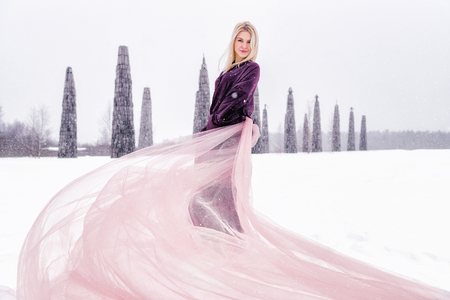 A girl stands in a field in winter. Train dress develops wind. Nikola-Lenivets, Russia