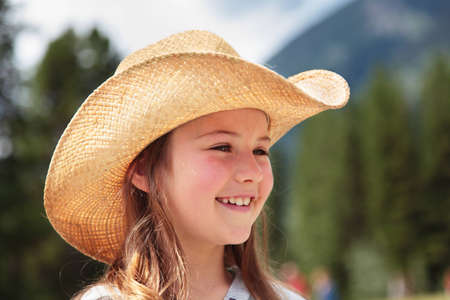A cowgirl laughing with trees and mountains in the background (the Rockies)