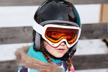 A girl wearing a skiing helmet and goggles photo