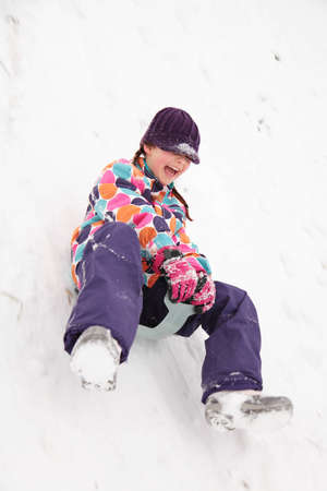 A girl coming down a hill on a plastic sled; slight motion blur photo