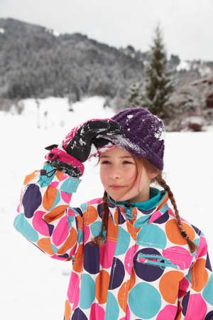 A girl brushing snow off her hat in the snow