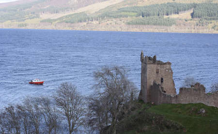 highland region: Urquhart Castle with a boat approaching on Loch Ness Stock Photo