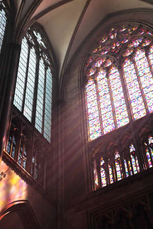 Beams of light in Cologne cathedral as the sun shines through the glass window.